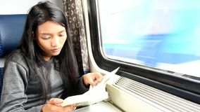 Passenger read book while traveling by train. Young woman with book sitting on the train, behind window a passing train stock footage