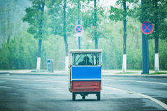Passenger rickshaw on the empty road at foggy morning time. Stock Image