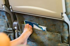 Passenger's leg placing on in front chair. Impolite behavior on stock images