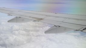Aerial View of Plane Wing High Above Clouds. A passenger`s perspective of looking out an airplane window at the wing, flying high above the clouds. Shot at 48fps stock video