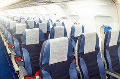 Passenger seat, Interior of airplane with passengers sitting on seats. Stock Photography