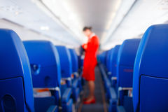 Passenger seat, Interior of airplane with passengers sitting on seats and stewardess walking the aisle in background. stewardess s stock photography