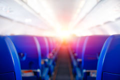 Passenger seat, Interior of airplane, plane flies to meet sun, bright sunlight illuminates the aircraft cabin, travel concept.  royalty free stock photography