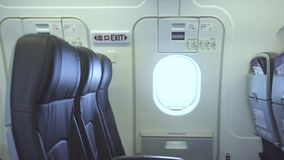 Passenger seats and emergency exit door inside commercial airplane. Interior modern passenger aircraft, passengers. Chairs and emergency door exit. Economy stock video footage