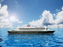 Passenger ship cruising at the sea. Against the blue cloudy sky Stock Images