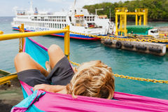Passenger on ship deck looking at public ferry at pier. Backpacker traveling lifestyle. Passenger relaxing in hammock on ship deck look at public ferry. Cars Stock Photos