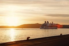 Passenger ship in sunset sea in Bergen, Norway. Passenger ship or ferry boat in sunset sea in Bergen, Norway. Cruise, journey, trip, wanderlust, vacation concept stock photos