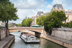 Passenger ship operated by Bateaux-Mouches on Seine river. Paris, France - August 11, 2014: White passenger touristic ship operated by Bateaux-Mouches goes under Stock Image