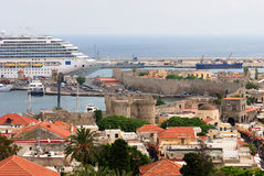 Passenger ship in port of old city. Modern nautical passenger ship in harbor of Rhodes city (Greece royalty free stock image