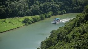 Passenger ship on a river in tropical forest stock footage