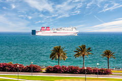Passenger ship sails along the promenade with palm trees Stock Image