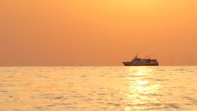 A passenger ship sails the sea on the horizon during sunset.  royalty free stock photography
