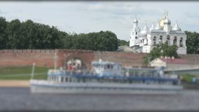Passenger ship with tourists floating on river. Passenger motor ship with tourists floating on Volhov river in summer in the background of Kremlin of Veliky stock video footage