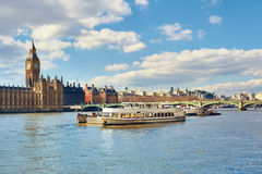 Passenger ships and service boats in front of Parliament of Lond Stock Photos