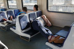 A passenger sleeping on a bench of a commuter train. Moscow region, Russia. Stock Image