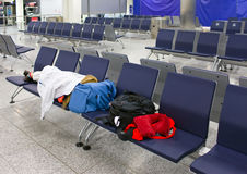 Passenger sleeps  in an empty night airport after flight cancellation Stock Photos