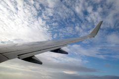 Passenger supersonic plane wing high moving from right to left in blue sky with clouds. Beautiful view from passenger supersonic airplane window moving high from Stock Photos