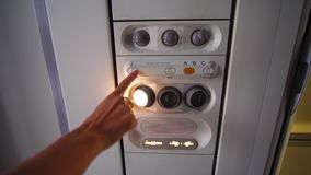 Passenger switches, reading lamp in airplane overhead panel.