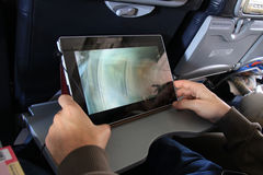 The passenger with tablet. The passenger relaxing using tablet inside airplane stock photos