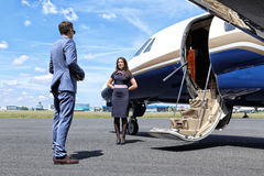 Passenger talking to stewardess in front of executive jet Royalty Free Stock Photography