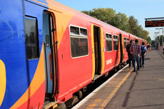Passenger train. East Molesey, UK – Oct 1, 2011: A South West train waiting for passengers to board at Hampton Court Station for its destination to Waterloo Royalty Free Stock Photo