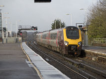 Passenger train approaching a railway station UK Stock Photos