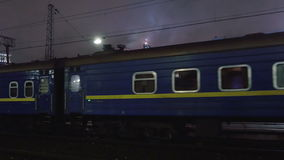 Passenger train arriving to station in the evening. Passenger train passing by slowly. It arriving to the station in the city in the dull evening stock footage