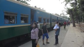 PASSENGER TRAIN: Blue passenger train waits on a shady platform. TRAIN LOCOMOTIVE: Blue passenger train waits on a shady platform, with passengers boarding and stock video footage