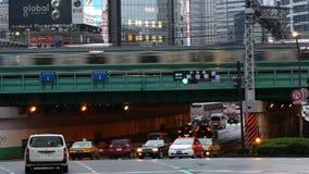 Passenger Train with Busy Street Traffic in Shinjuku - Tokyo Japan. Famous City of Shinjuku - Tokyo Japan stock video
