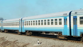 Passenger train with carriages passing by from distancing away. Coming in front of stock footage