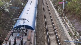 Passenger train coming. Brno, Czech Republic - April 15, 2018: Passenger train passing under an overpass, slowing down to a station stock footage