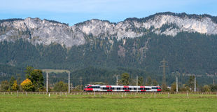 Passenger train goes in the Austrian Alps. Stock Images