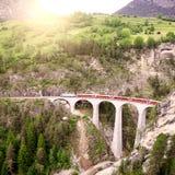 Passenger train goes from St. Moritz to Chur. Passenger train goes from St. Moritz to Chur on Landwasser viaduct stock photo
