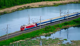 Passenger train between lakes. Red, blue passenger train between lakes. Top view. Long structure from first-class sleepers. Airview Royalty Free Stock Photography