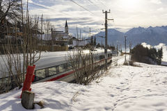 Passenger train and mountains during winter. Fast moving passenger train moving towards beautiful mountain range with bright sun during winter stock images