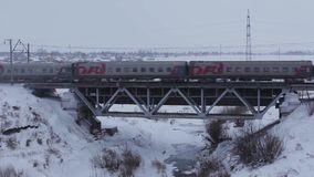 Passenger Train in movement on bridge in winter stock video