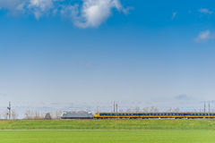 Passenger Train Moving along Green Field. High-speed passenger train moving along green field. Transportation and travel theme. Railway transport Royalty Free Stock Images