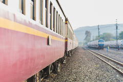 Passenger train. Of Thai Railways. The nearest purple car is in the focus, other things dissolve into nice bokeh. This is a second class sitting car of a train Royalty Free Stock Images