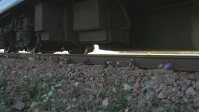 Passenger train passes by a camera. Wheels of the train moving along the rails closeup. Close-up shot of a passenger stock video footage