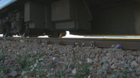 Passenger train passes by a camera. Wheels of the train moving along the rails closeup. Close-up shot of a passenger stock footage