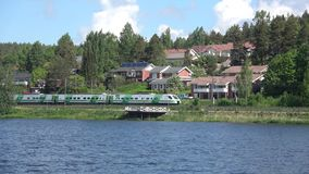 Passenger train passes through the city of Hameenlinna, Finland stock footage