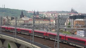 Passenger train passes through the railway overpass on the background of the old city. Prague. PRAGUE, CZECH REPUBLIC - APRIL 23, 2018: Passenger train passes stock footage