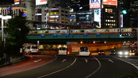Passenger Train Passes the Shinjuku Skyline at Night - Tokyo Japan. Famous City of Shinjuku - Tokyo Japan stock video