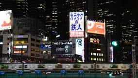 Passenger Train Passes the Shinjuku Skyline at Night - Tokyo Japan. Famous City of Shinjuku - Tokyo Japan stock footage