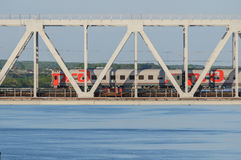 Passenger train passing the bridge over the river in summer. Passenger railway cars on the bridge across the river in summer Royalty Free Stock Photography