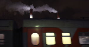 Passenger train passing by factory at night stock footage
