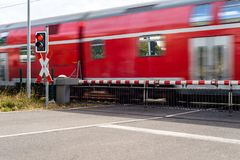 A passenger train passing through a guarded railway crossing with closed barriers and a red light. stock photos