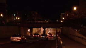 Passenger train passing over cars on an underpass stock video