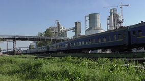 Passenger train is moving. Passenger train is passing past the cement plant stock footage