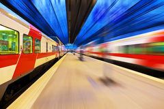 Passenger train passing railway station Royalty Free Stock Image